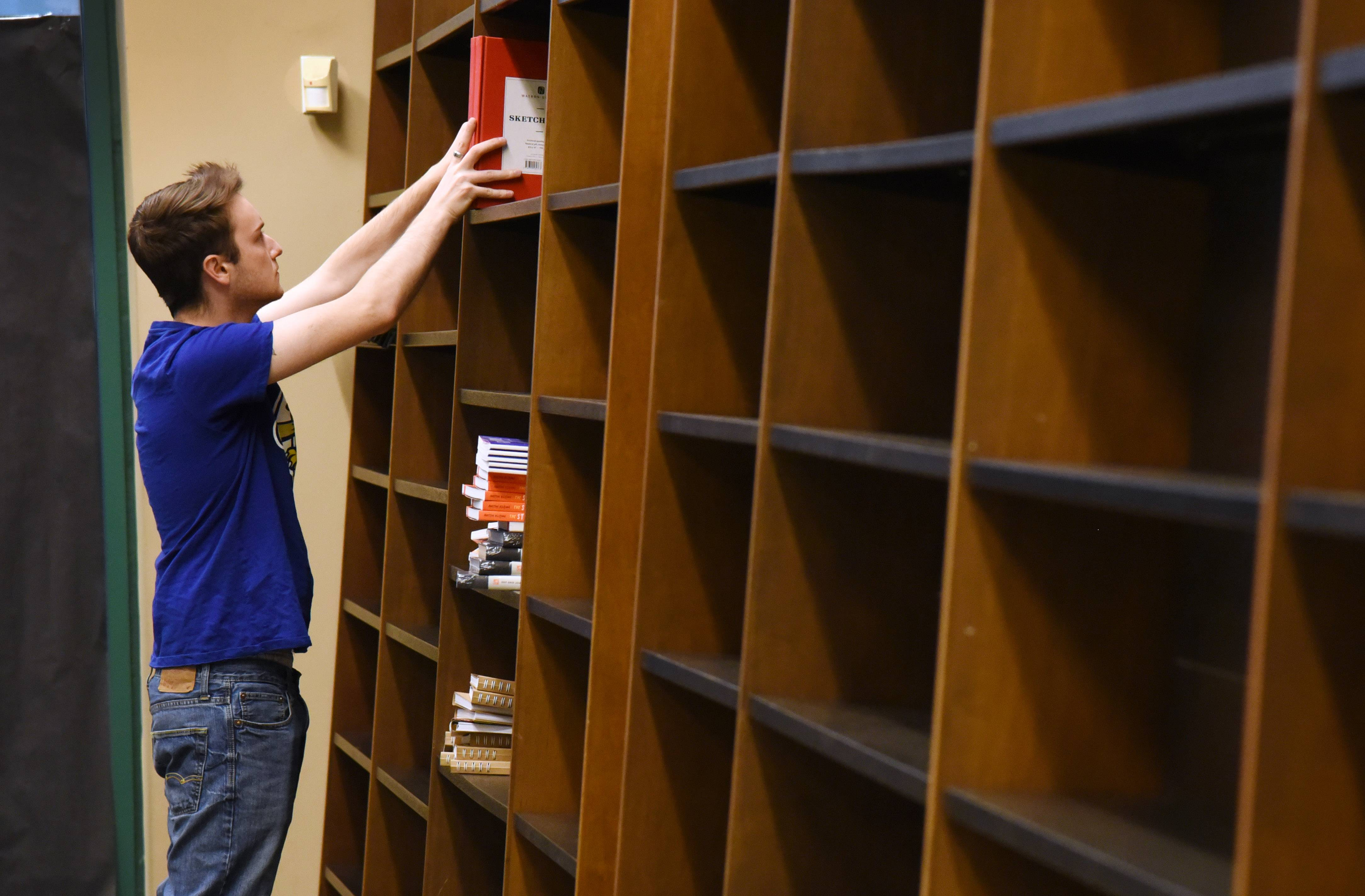 Barbara's Bookstore senior bookseller Ryan Morris fills wall shelves Monday to prepare for the store's Wednesday opening in the former Barnes & Noble space at Hawthorn Mall in Vernon Hills.