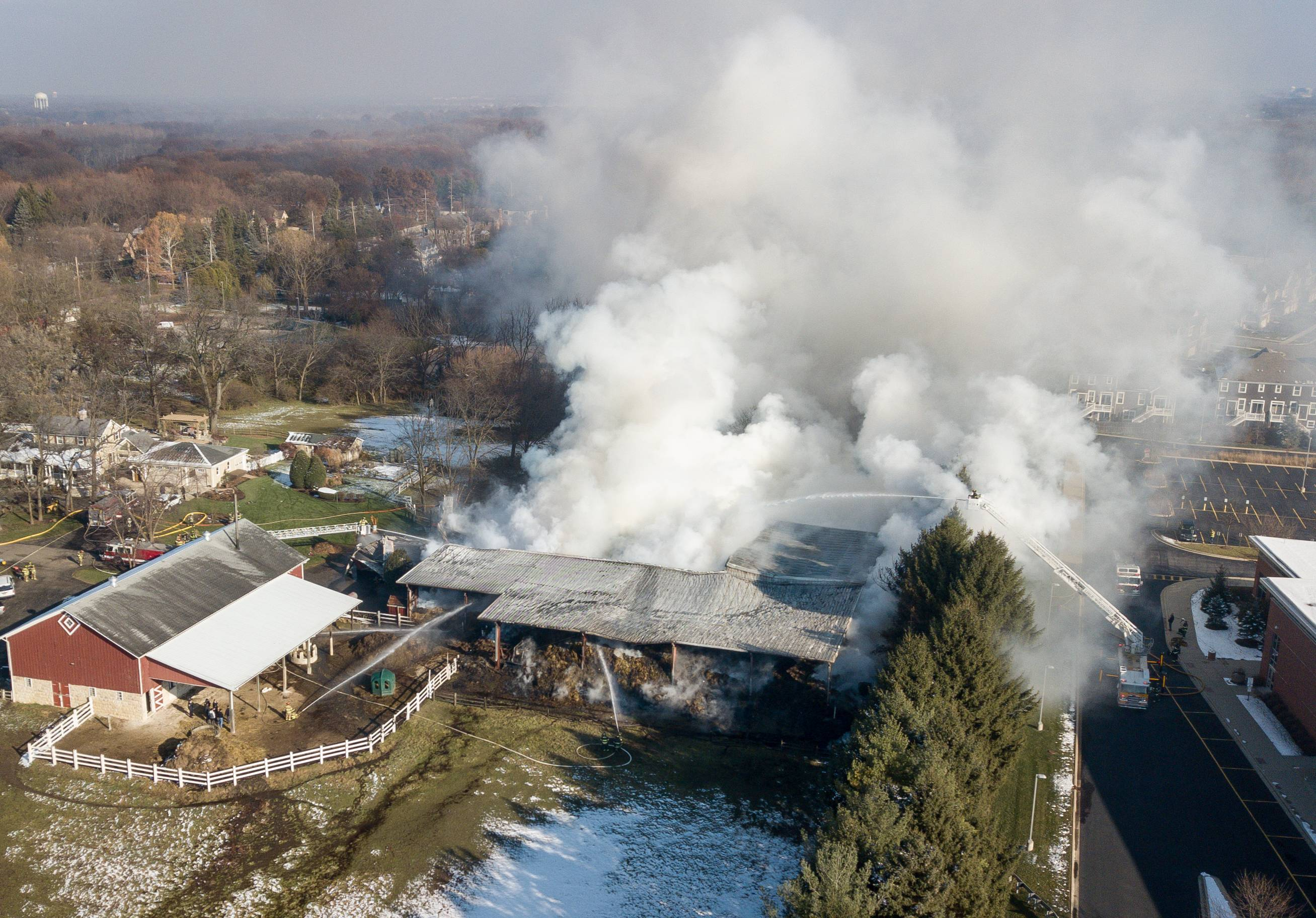 Firefighters are expected to remain at Galusha Farm near Warrenville through Wednesday to put out fires still smoldering in the hay barn that caught fire Monday morning.