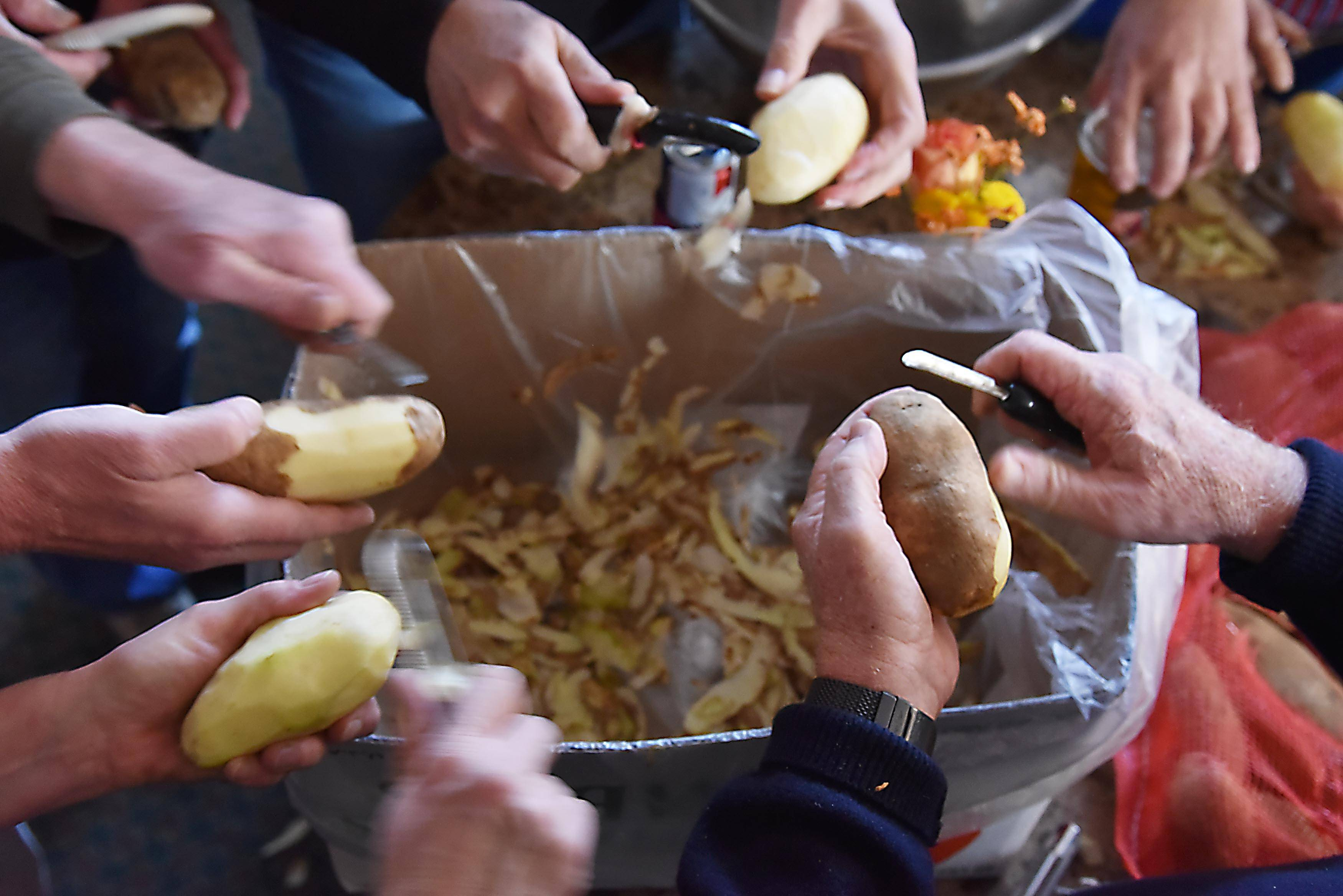 Volunteers peel hundreds of pounds of potatoes Tuesday at Barrington's Blue Heron Cafe before delivery of Thanksgiving meals to those in need in the area.