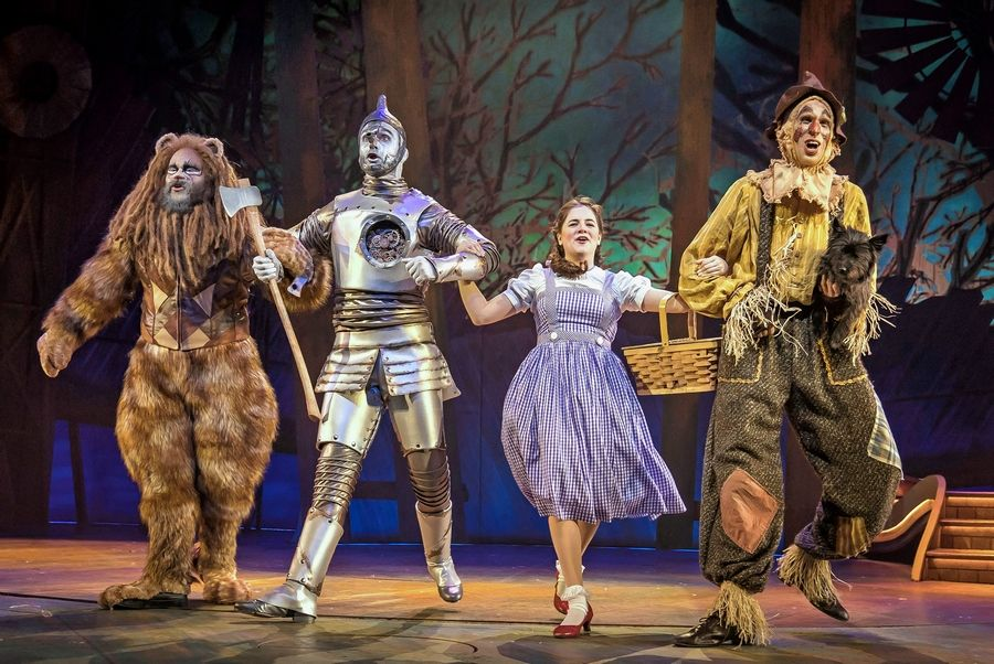 "Paul-Jordan Jansen, left, plays Cowardly Lion, Carl Draper is Tinman, Elizabeth Stenholt plays Dorothy, Kyle Adams is Scarecrow and Nessa is Toto in Paramount Theatre's ""The Wizard of Oz,"" directed and choreographed by Amber Mak."