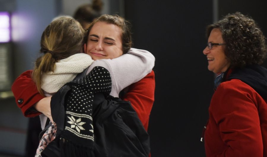 Kristen Slevnik of Naperville, facing, embraces childhood friend Beatriz Servulo, who arrived on a flight from South Carolina on Wednesday at O'Hare International Airport. Donna Slevnik, Kristen's mom, waits to get a hug.