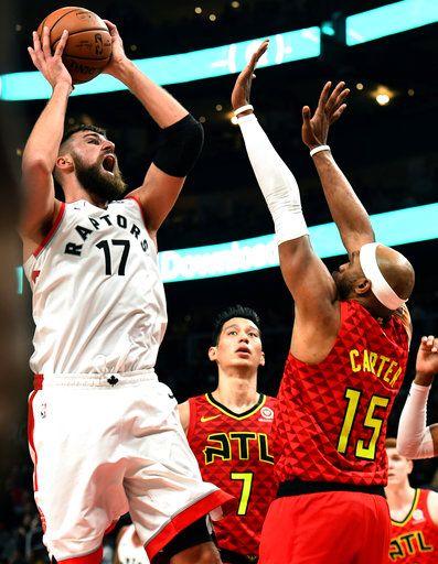 ece87cb3741 Toronto Raptors center Jonas Valanciunas (17) shoots as Atlanta Hawks  forward Vince Carter (