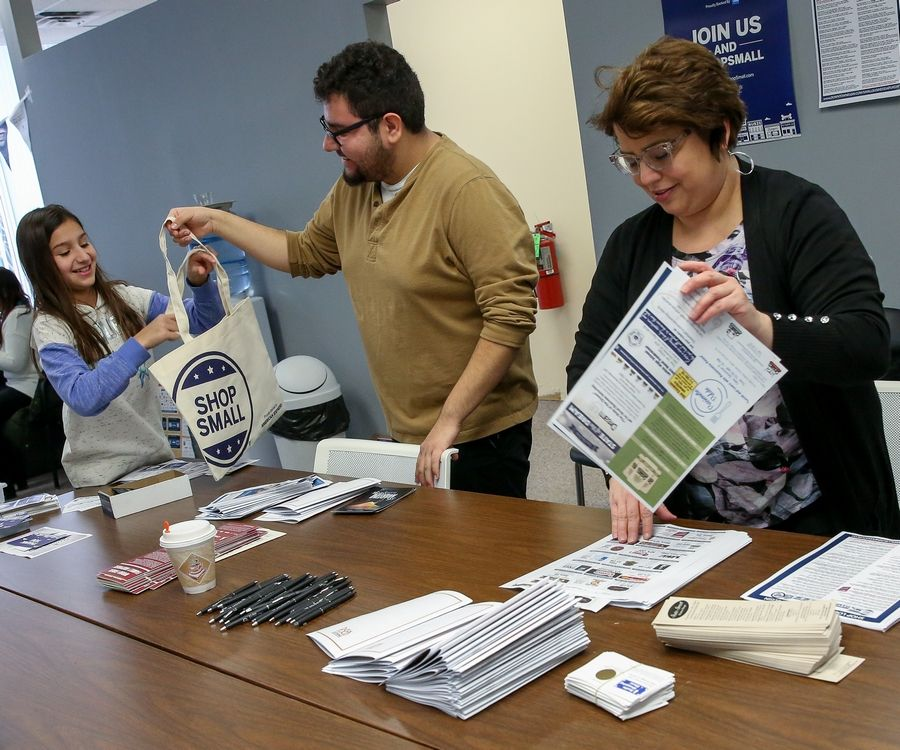 Left to right, Isabella Shababy, 11, Eduardo Jaramillo and Cynthia Shababy, volunteers with Downtown Neighborhood Association of Elgin, stuff coupons and flyers for Small Business Saturday promotion.