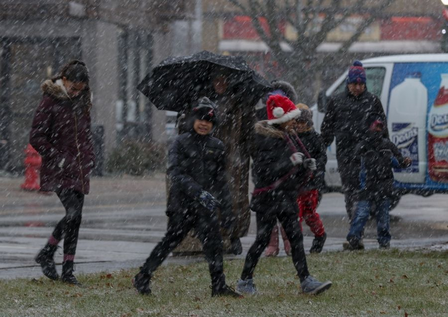 Snow falls Sunday as people arrive for the Holiday Magic Celebration in Bensenville. Forecasters predicted the mix of rain and snow that passed through the suburbs for much of the day would turn to heavy snow overnight.
