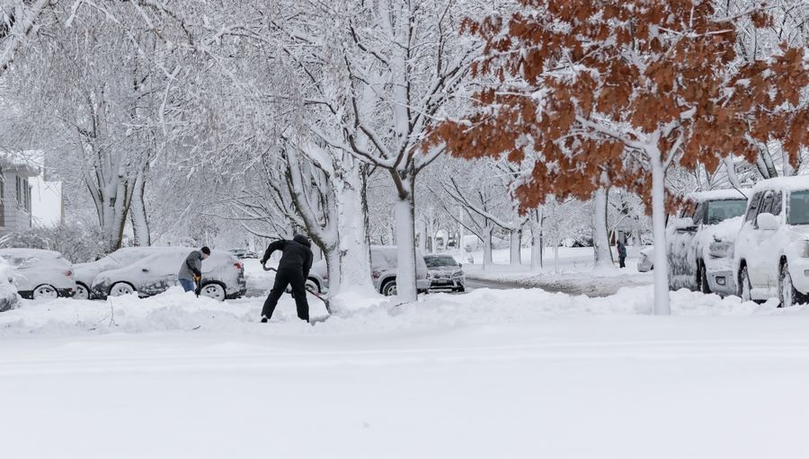 People dig out after heavy snow in Arlington Heights on Monday.