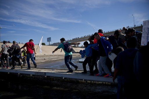 Migrants cross the river at the Mexico-U.S. border after getting past a line of Mexican police at the Chaparral crossing in Tijuana, Mexico, Sunday, Nov. 25, 2018, as they try to reach the U.S.  The mayor of Tijuana has declared a humanitarian crisis in his border city and says that he has asked the United Nations for aid to deal with the approximately 5,000 Central American migrants who have arrived in the city.