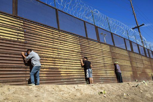 Migrants peer through the border wall after pushing past Mexican police at the Chaparral crossing in Tijuana, Mexico, Sunday, Nov. 25, 2018, as they try to reach the U.S. The mayor of Tijuana has declared a humanitarian crisis in his border city and says that he has asked the United Nations for aid to deal with the approximately 5,000 Central American migrants who have arrived in the city.