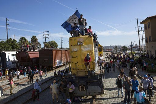 A migrant waves an Honduran flag along the railroad tracks at the Mexico-U.S. border in Tijuana, Mexico, Sunday, Nov. 25, 2018, as a group of migrants tries to reach the U.S.  The mayor of Tijuana has declared a humanitarian crisis in his border city and says that he has asked the United Nations for aid to deal with the approximately 5,000 Central American migrants who have arrived in the city.