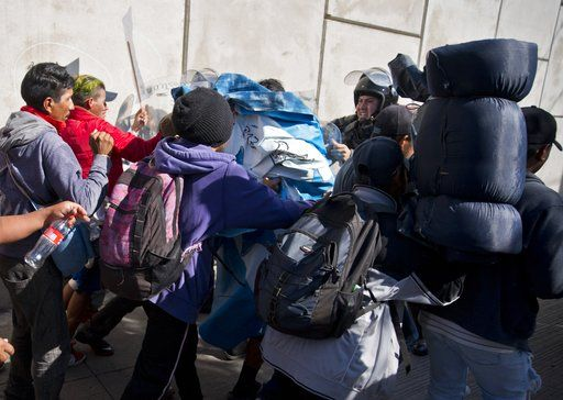 Migrants push past Mexican police at the Chaparral border crossing in Tijuana, Mexico, Sunday, Nov. 25, 2018, as they try to reach the United States. The mayor of Tijuana has declared a humanitarian crisis in his border city and says that he has asked the United Nations for aid to deal with the approximately 5,000 Central American migrants who have arrived in the city.