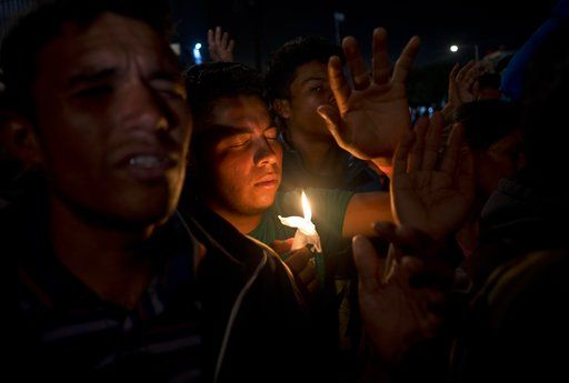 Migrants pray during a vigil outside the Benito Juarez Sports Center serving as a temporary shelter for Central American migrants in Tijuana, Mexico, Saturday, Nov. 24, 2018. The mayor of Tijuana has declared a humanitarian crisis in his border city and says that he has asked the United Nations for aid to deal with the approximately 5,000 Central American migrants who have arrived in the city.