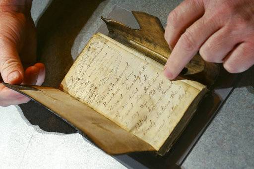This photo taken Nov. 14, 2018, shows a diary that Randy Smith holds open at the Howard County Historical Society in Kokomo, Indiana, where he is assistant curator. The Kokomo Howard County Public Library are scanning and cataloging for the Indiana Memory Project in Kokomo, Ind. Items on display at the Howard County Historical Society will be photographed and documented on the online site. (Tim Bath/The Kokomo Tribune via AP)