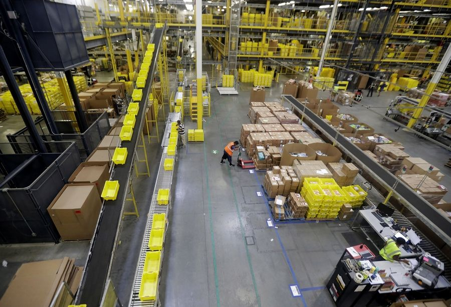 Amazon this month boosted its minimum wage for all U.S. workers, like those seen above in an Amazon distribution center, to $15 per hour. That's the same amount Gov.-elect J.B. Pritzker says he will work to put in place across Illinois.