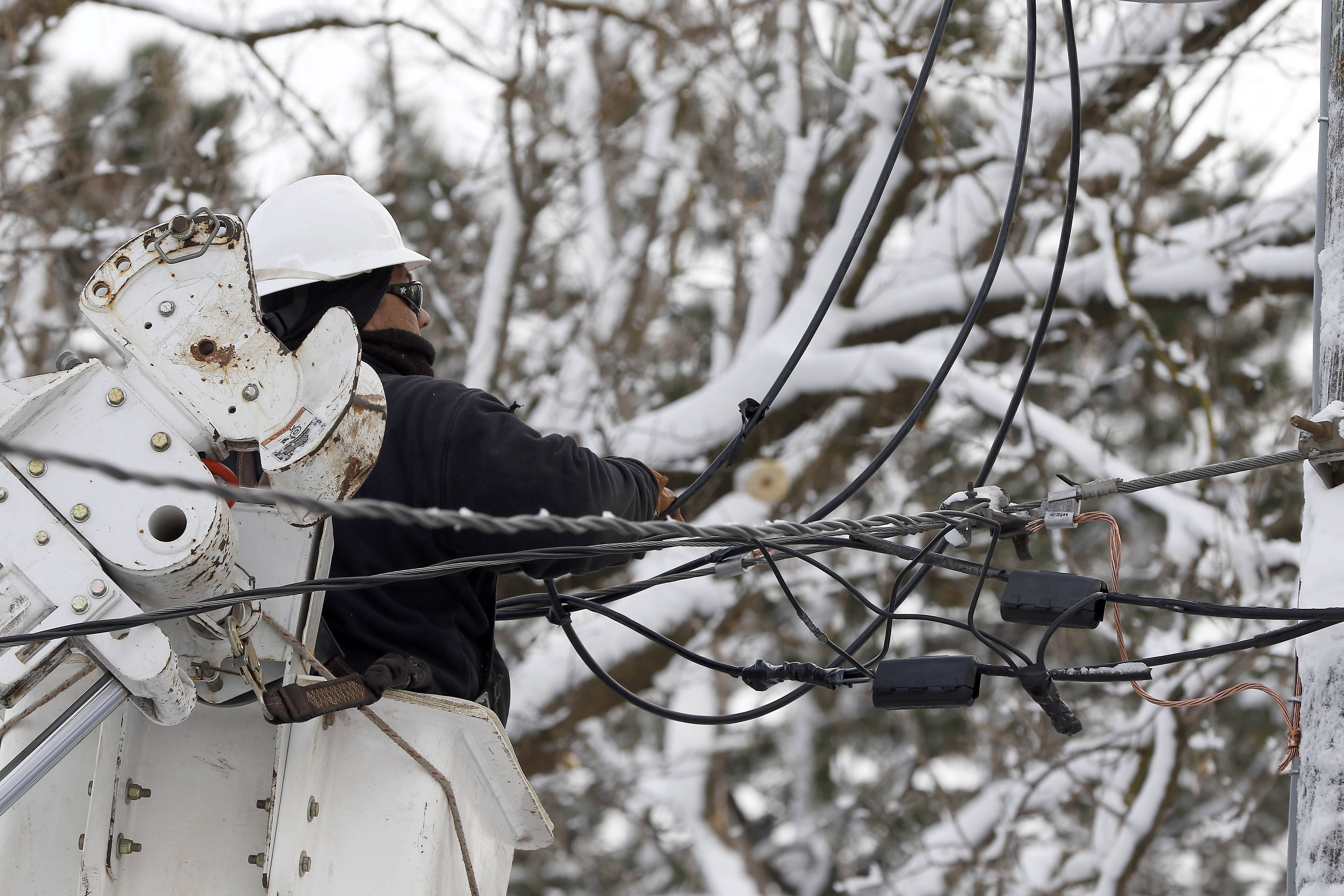 David Roy Ochoa repairs a transformer on the 700 block of Cordial Drive in Des Plaines Wednesday. He is part of an Intren crew from Bolingbrook that was contracted by ComEd after 350,000 customers lost power.