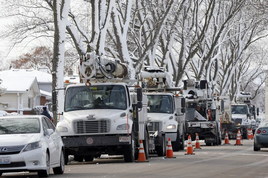 Workers from Bolingbrook-based Intren repair storm damage to restore power in Des Plaines Wednesday.