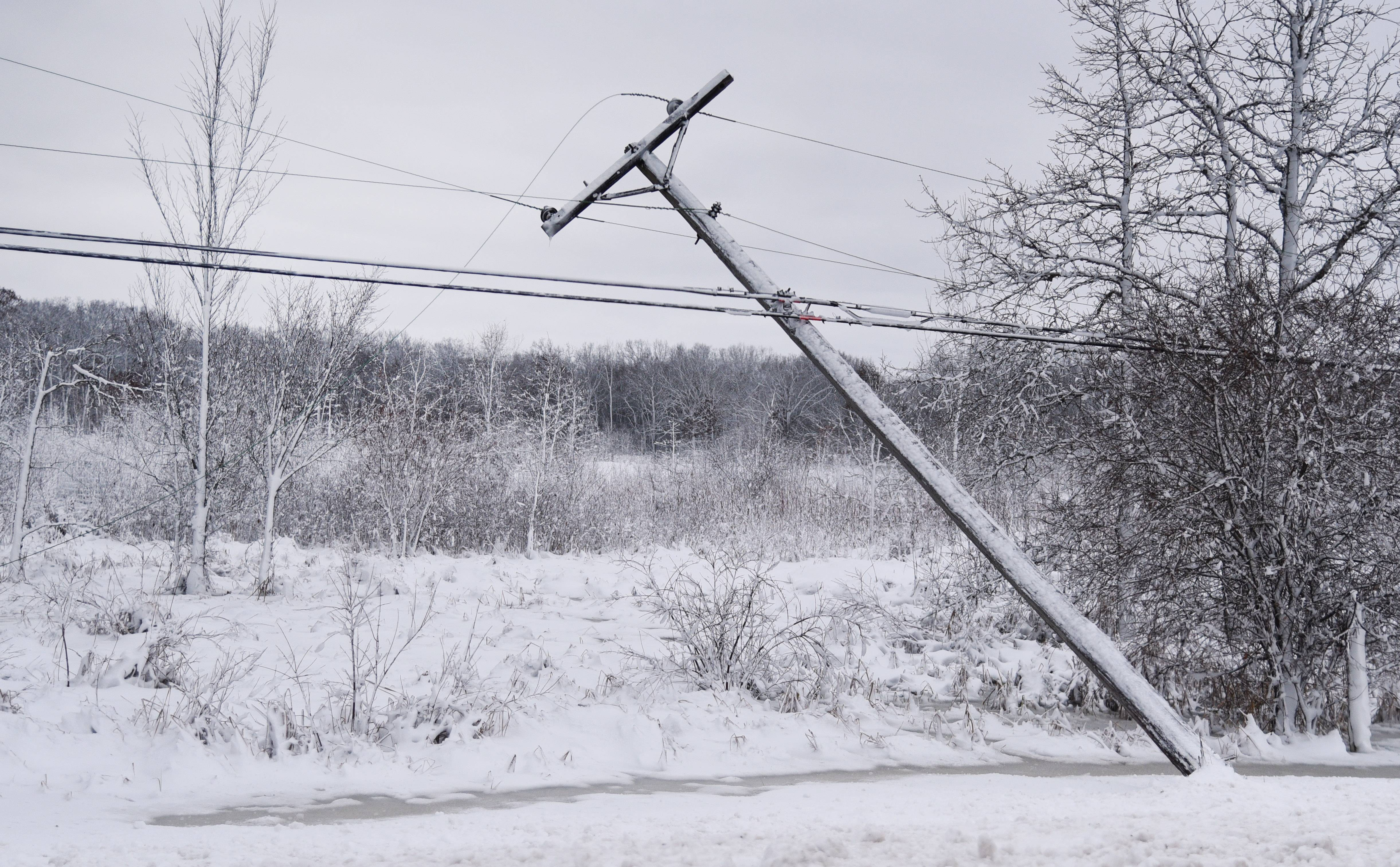 Thousands of people remain without electricity days after an ice and snowstorm hit the region, damaging power lines and poles like this one along Everett Road just west of Riverwoods Road near Lincolnshire.