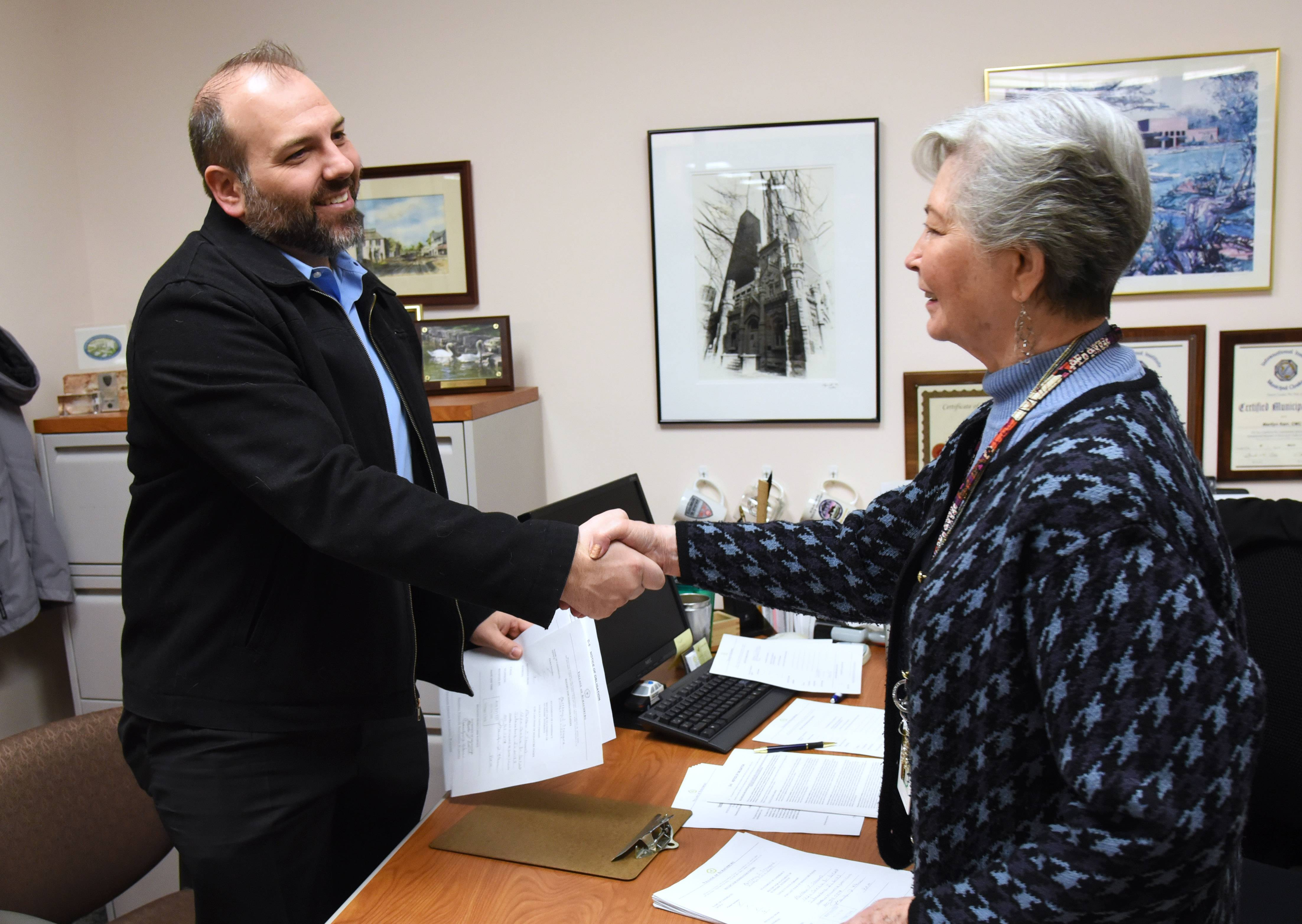 Matthew Steward, left, thanks Schaumburg Village Clerk Marilyn Karr after he filed his paperwork to run in the April 2 election earlier this month. Most other towns require nominating papers to be filed Dec. 10-17.