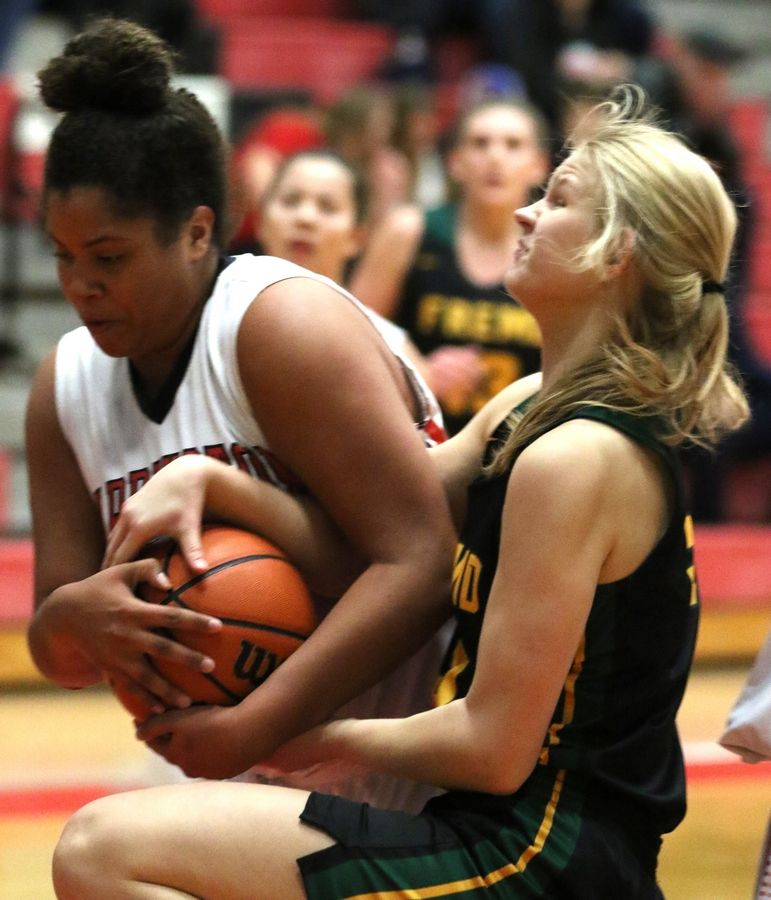 Barrington's Taylor Thompson, left, gets tangled up with Fremd's Ruthie Montella during varsity girls basketball in Barrington on Friday night.
