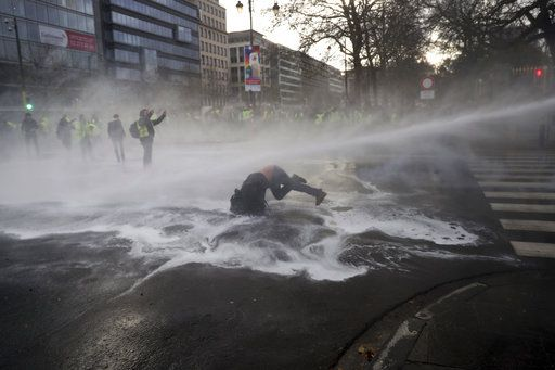 A demonstrator gets hit by a water cannon during a protest of the yellow jackets in Brussels, Friday, Nov. 30, 2018. The demonstrators are protesting against rising fuel prices.