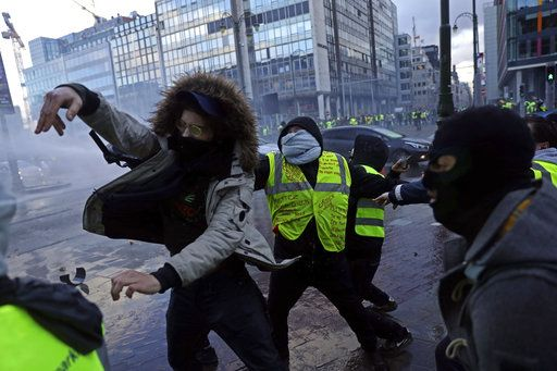 Demonstrators throw rocks during a protest of the yellow jackets in Brussels, Friday, Nov. 30, 2018. The demonstrators are protesting against rising fuel prices.