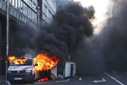 Demonstrators light a police van on fire during a protest of the yellow jackets in Brussels, Friday, Nov. 30, 2018. The demonstrators are protesting against rising fuel prices.