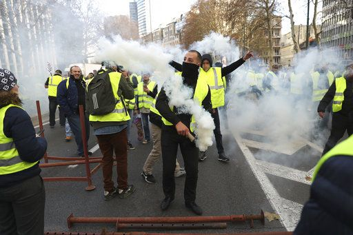 Demonstrators, called the yellow jackets, light flares and shout slogans as they protest against rising fuel prices in Brussels, Friday, Nov. 30, 2018