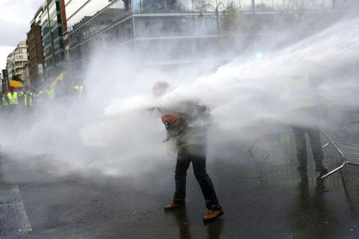 Police use a water cannon on demonstrators during a protest of the yellow jackets in Brussels, Friday, Nov. 30, 2018. The demonstrators are protesting against rising fuel prices.