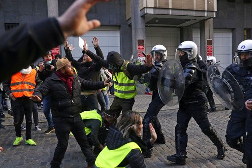Anti riot policemen push protestors back during a protest of the yellow jackets in Brussels, Friday, Nov. 30, 2018. The demonstrators are protesting against rising fuel prices.