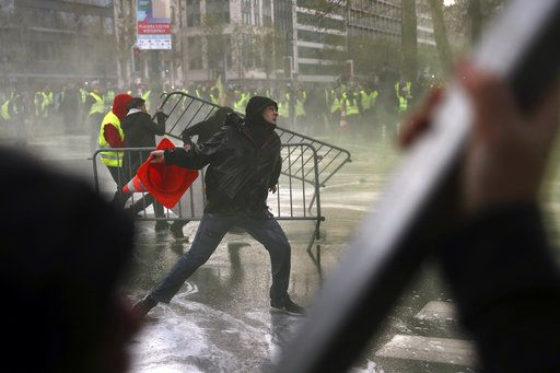 A demonstrator throws a traffic cone during a protest of the yellow jackets in Brussels, Friday, Nov. 30, 2018. The demonstrators are protesting against rising fuel prices.