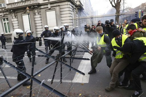 Police spray tear gas at demonstrator during a protest of the yellow jackets in Brussels, Friday, Nov. 30, 2018. The demonstrators are protesting against rising fuel prices.
