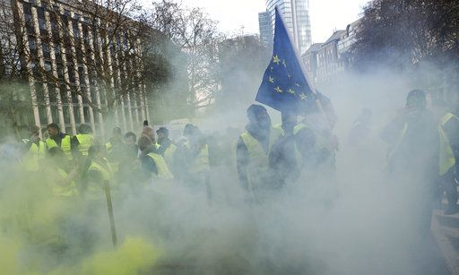 Demonstrators, called the yellow jackets, holds up an EU flag during a protest against rising fuel prices in Brussels, Friday, Nov. 30, 2018