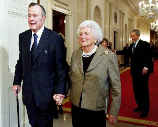 FILE - In this Jan. 7, 2009, file photo, former President George H. W. Bush, left, walks with his wife, former first lady Barbara Bush, followed by their son, President George W. Bush, and his wife first lady Laura Bush, to a reception in honor of the Points of Light Institute, in the East Room at the White House in Washington. Bush died at the age of 94 on Friday, Nov. 30, 2018, about eight months after the death of his wife, Barbara Bush.