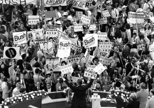 FILE - In this July 16, 1980 file photo George H.W. Bush, center foreground, acknowledges the crowd before speaking to the Republican Convention delegates in Detroit, Mich. Bush died at the age of 94 on Friday, Nov. 30, 2018, about eight months after the death of his wife, Barbara Bush.