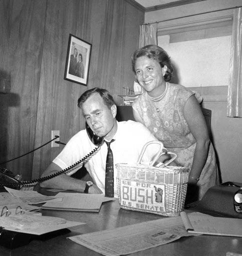 FILE - In this June 6, 1964, file photo George H.W. Bush, candidate for the Republican nomination for the U.S. Senate, gets returns by phone at his headquarters in Houston, as his wife Barbara, smiles at the news. Bush died at the age of 94 on Friday, Nov. 30, 2018, about eight months after the death of his wife, Barbara Bush.