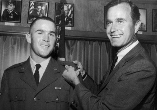 FILE - In this 1968 file photo provided by the Texas National Guard, George H.W. Bush, right, is about to pin a lieutenant bar on his son, George W. Bush, after the younger Bush was made an officer in the Texas Air National Guard in Ellington Field, Texas. Bush died at the age of 94 on Friday, Nov. 30, 2018, about eight months after the death of his wife, Barbara Bush.