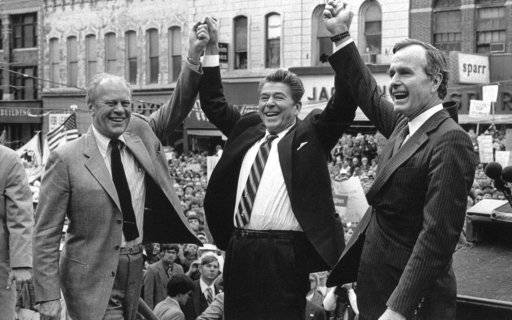 FILE - In this Nov. 3, 1980, file photo, former President Gerald Ford lends his support to Republican presidential candidate Ronald Reagan and his running mate, George H.W. Bush in Peoria, Ill. Bush has died at age 94. Family spokesman Jim McGrath says Bush died shortly after 10 p.m. Friday, Nov. 30, 2018, about eight months after the death of his wife, Barbara Bush.