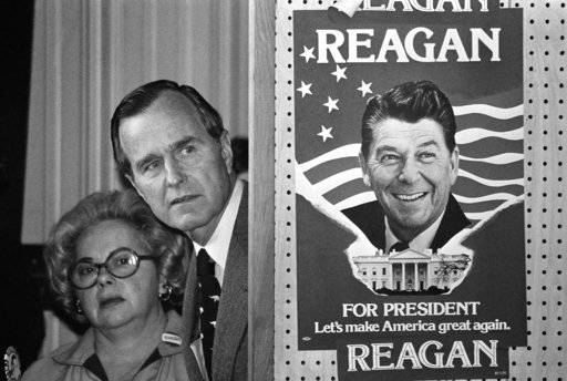 FILE - In this March 4, 1980 file photo, George H.W. Bush and an unidentified woman peek around a partition with a poster of Ronald Reagan, one of his opponents for the Republican party presidential nomination, before he speaks in Columbia, S.C. Bush has died at age 94. Family spokesman Jim McGrath says Bush died shortly after 10 p.m. Friday, Nov. 30, 2018, about eight months after the death of his wife, Barbara Bush.