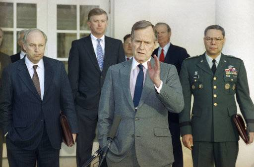 FILE - In this Feb. 11, 1991, file photo, President George H.W. Bush talks to reporters in the Rose Garden of the White House after meeting with top military advisors to discuss the Persian Gulf War. From left are, Defense Secretary Dick Cheney, Vice President Dan Quayle, White House Chief of Staff John Sununu, the president, Secretary of State James A. Baker III, and Joint Chiefs Chairman Gen. Colin Powell. Bush died at the age of 94 on Friday, Nov. 30, 2018, about eight months after the death of his wife, Barbara Bush.