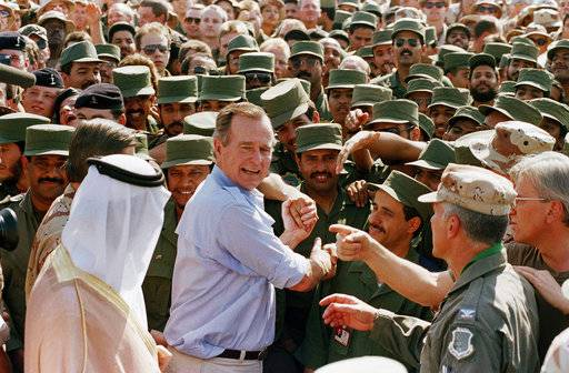 FILE - In this Nov. 22, 1990 file photo, President George H.W. Bush is greeted by Saudi troops and others as he arrives in Dhahran, Saudi Arabia, for a Thanksgiving visit. Bush died at the age of 94 on Friday, Nov. 30, 2018, about eight months after the death of his wife, Barbara Bush.