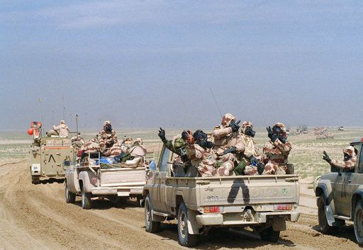"FILE - In this Feb. 24, 1991 file photo, Kuwaiti troops wear gas masks and protective suits as they roll through southern Kuwait in an armed motor convoy, the first full day of ground conflict in Operation Desert Storm. The inverted ""V"" painted on vehicles is the allied recognition symbol. In February 1991, after months of building an international coalition, U.S. forces entered Kuwait to end the Iraqi occupation of its smaller, oil-rich neighbor."