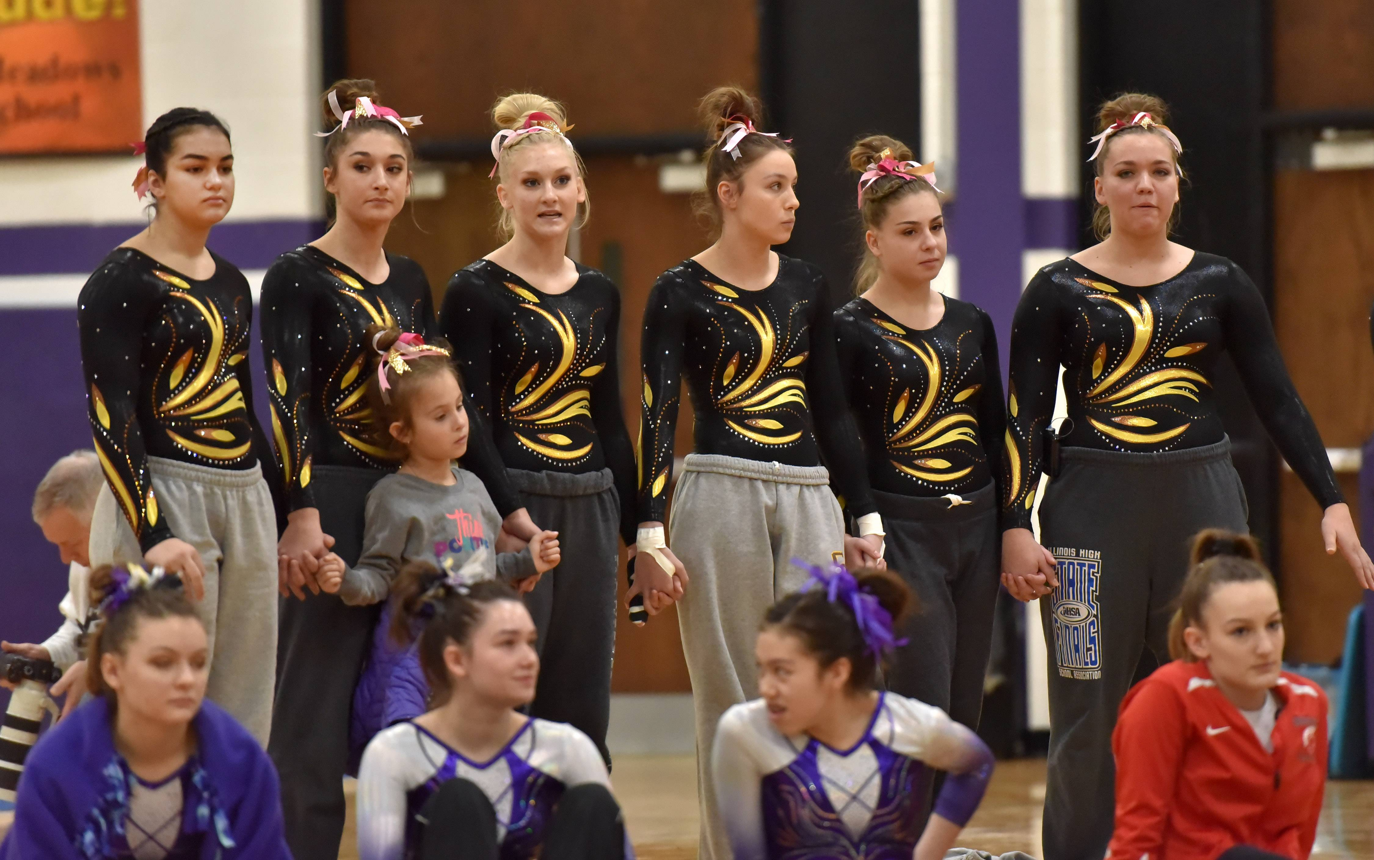 Part of the Carmel Catholic High School team hold hands as they watch a teammate Saturday at the Rolling Meadows High School girls gymnastics Al Galatte Holiday Invitational.