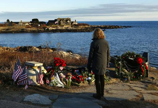 Cathy Rogers of Windham, Maine, pays her respects at a makeshift memorial for President George H. W. Bush across from Walker's Point, the Bush's summer home, Saturday, Dec. 1, 2018, in Kennebunkport, Maine. Bush died at the age of 94 on Friday, about eight months after the death of his wife, Barbara Bush.