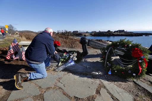 A man pays his respects to former President George H. W. Bush at a makeshift memorial across from Walker's Point, the Bush's summer home, Saturday, Dec. 1, 2018, in Kennebunkport, Maine. Bush died at the age of 94 on Friday, about eight months after the death of his wife, Barbara Bush.