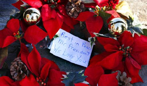 A wreath with a note to former President George H. W. Bush lay at a makeshift memorial across from Walker's Point, the Bush's summer home, Saturday, Dec. 1, 2018, in Kennebunkport, Maine. Bush died at the age of 94 on Friday, about eight months after the death of his wife, Barbara Bush.