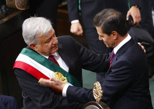 Mexico's new President Andres Manuel Lopez Obrador and outgoing President Enrique Pena Nieto embrace at the end of the swearing-in ceremony in the lower house chambers of the National Congress, in Mexico City, Saturday, Dec. 1, 2018. Lopez Obrador took the oath of office Saturday as Mexico's first leftist president in over 70 years, marking a turning point in one of the world's most radical experiments in opening markets and privatization.