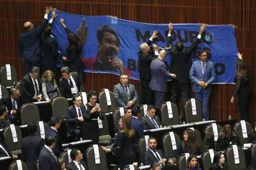 "Conservative legislators tape a banner with a message that reads in Spanish: ""(Nicolas) Maduro, you're not welcome� to a wall in the lower house of Congress, just a couple of hours before the Venezuelan leader is scheduled to attend the inauguration of President-elect Andres Manuel Lopez Obrador, at the National Congress in Mexico City, Saturday, Dec 1, 2018. Mexico's conservative National Action Party has voiced objections to Lopez Obrador's decision to invite Maduro to the ceremony, because of the economic and political crisis that has marked Maduro's regime."