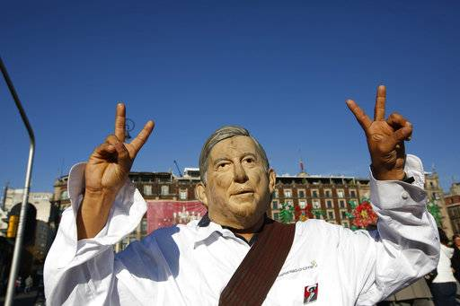 "A man wearing a mask depicting Mexico's new President Andres Manuel Lopez Obrador flashes ""vee for victory"" hand signs as he arrives at the Zocalo where celebrants are gathering for the presidential inaugural festivities, in Mexico City, Saturday, Dec. 1, 2018.  Mexicans are getting more than just a new president Saturday. The inauguration of Lopez Obrador will mark a turning point in one of the world's most radical experiments in opening markets and privatization."