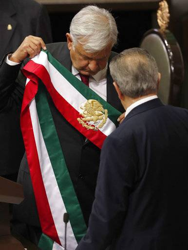 Mexico's new President Andres Manuel Lopez Obrador holds the presidential sash after taking the oath of office at the National Congress during his inauguration ceremony in Mexico City, Saturday, Dec. 1, 2018. Lopez Obrador took the oath of office Saturday as Mexico's first leftist president in over 70 years, marking a turning point in one of the world's most radical experiments in opening markets and privatization.