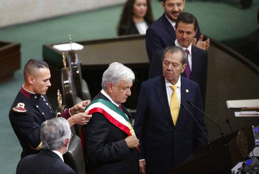 Mexico's outgoing President Enrique Pena Nieto, wearing striped tie, and Porfirio Munoz Ledo, president of the lower house of Congress, wearing yellow tie, watch as a military cadet arranges the presidential sash on Mexico's incoming President Andres Manuel Lopez Obrador at the National Congress during the presidential inauguration ceremony in Mexico City, Saturday, Dec. 1, 2018.