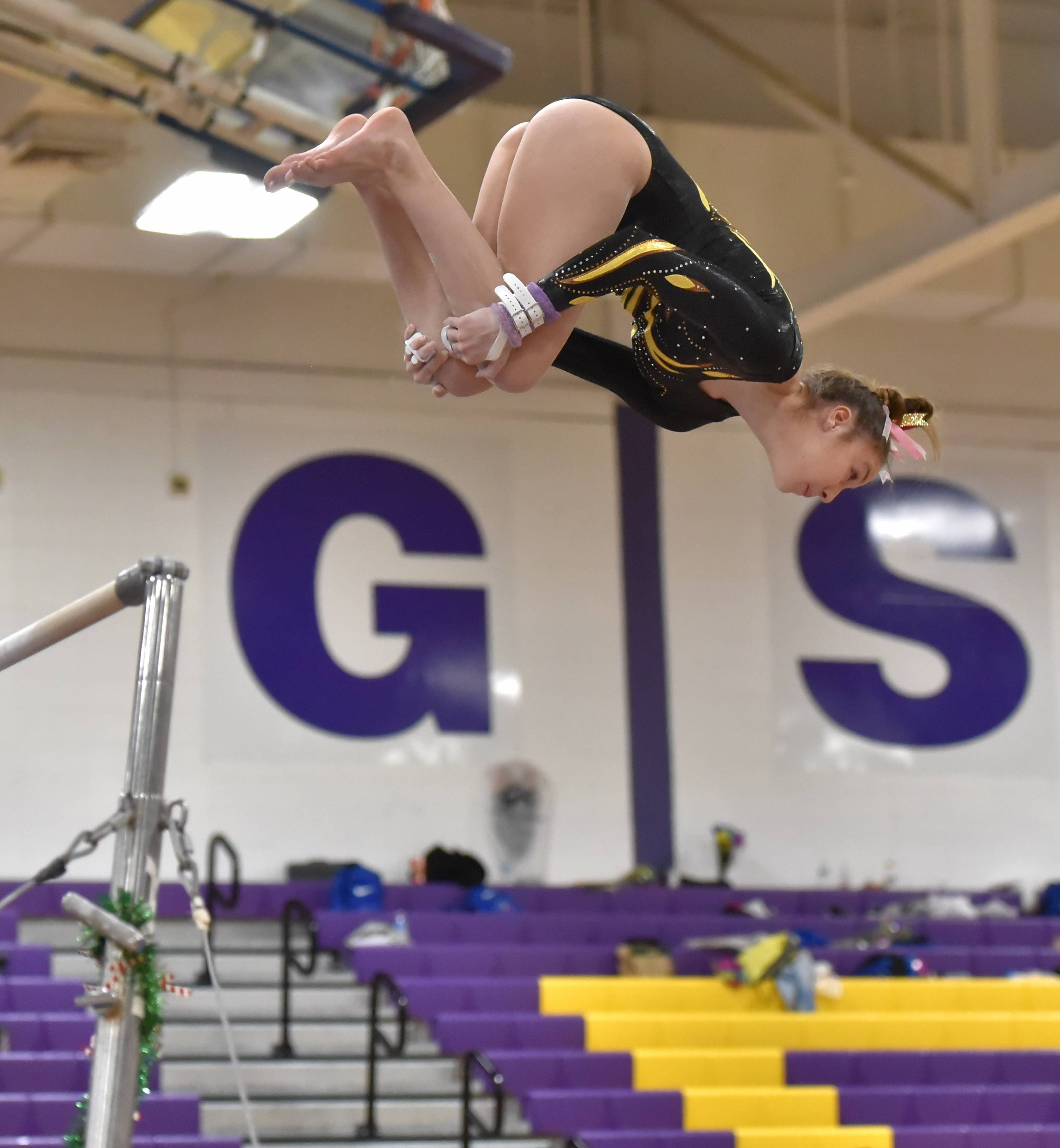 Carmel's Clare Keane performs on the Uneven Parallel Bars Saturday at the Rolling Meadows High School girls gymnastics Al Galatte Holiday Invitational.
