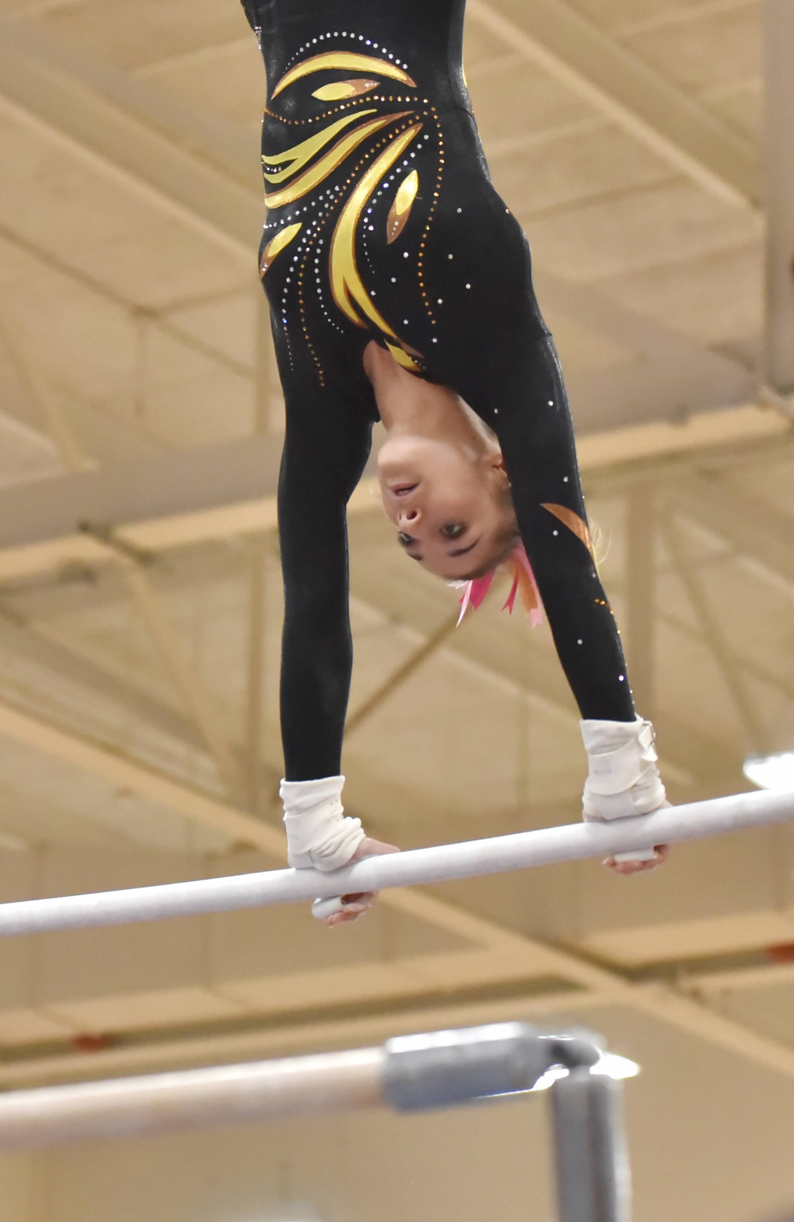 Carmel's Izzy Kropiwiec performs on the Uneven Parallel Bars Saturday at the Rolling Meadows High School girls gymnastics Al Galatte Holiday Invitational.